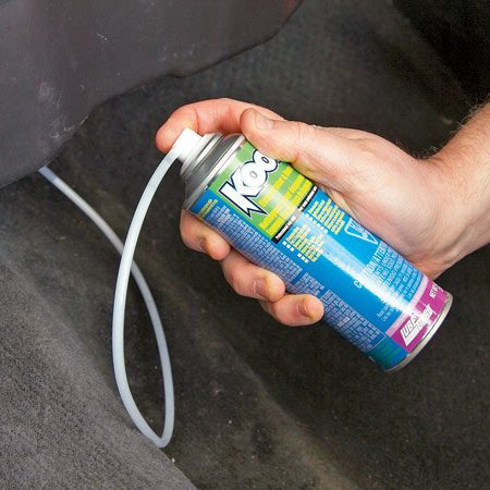 <b>Photo 10: Inject mold-killing foam</b><br/>Thread the plastic hose into your A/C evaporator case. Then shake the can and depress the valve until the can is empty. Replace the drain hose and any other parts you removed.