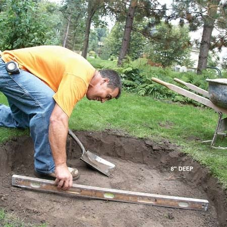 <b>Photo 2: Level the pit</b></br> Check the bottom of the hole with a level. Remove high spots by scraping off soil rather than digging. That way, you won't loosen the underlying soil. Compact the soil with a hand tamper or a 4x4 post.
