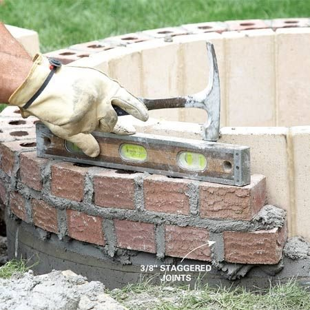 <b>Photo 11: Work in sections</b></br> Working on one-third of the pit at a time, check the level of each course and tap down the bricks as necessary. Stagger the joints between courses for strength.