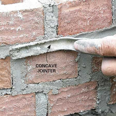 "<b>Photo 12: Strike the joints</b></br> After you finish each section of face brick, use a jointer to smooth (""strike"" or ""tool"") the joints before the mortar dries too much. The mortar is ready to strike if you press your finger into it and the indentation remains. Striking gives the wall a uniform, polished look."