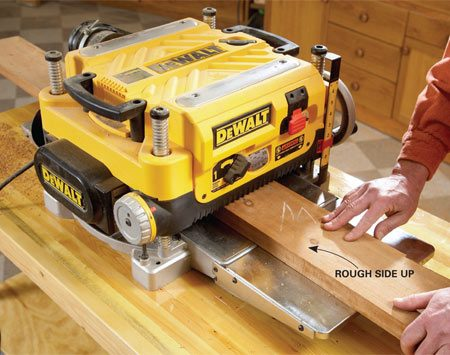 <b>Photo 3: Flatten the opposite side</b></br> <p>Send the highest point (at either end) of  the board through the planer first, with a very   small cut. Sneak up on the cutting  depth; there are likely to be high spots that might   stall the planer as they come through  the knives. After the first pass, you can cut a bit   deeper, but shallower passes will be  less taxing on the tool and less likely to produce   tear-out, stalls and burning. As with  the jointer, swing the board around and send the   other end through if you get any  tear-out. Before you get to the final thickness, plane   out any  tear-out on the first side. </p>