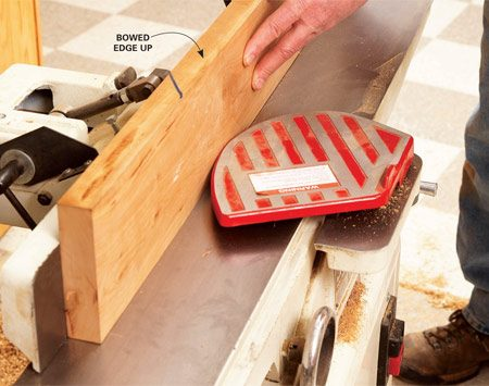 <b>Photo 4: Flatten one edge</b></br> Sight the board to find any bows. Hold the board against the fence with the bowed side up and send it through the jointer just as you did for the sides. Stop when the edge is flat.