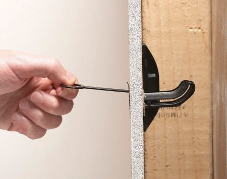 <b>Pull anchor tight</b></br> Pull the anchor against the back of the drywall with the pull tool, then screw the TV mounting bracket to it.
