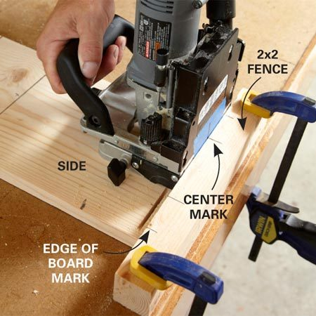 <b>Photo 3: Slot the end of the side</b></br> Clamp the fence to the work surface and butt the end of the shelf to it. Then center the biscuit joiner on the mark and cut the slot. Repeat for the second slot.