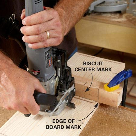 <b>Photo 4: Cut slots for the shelves</b></br> Line up the 2x2 jig with the edge of board mark and clamp it. Center the biscuit joiner on the center mark on the fence and cut the slot. Repeat for the second slot.