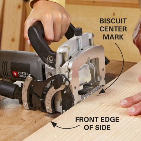 <b>Photo 5: Cut slots for the legs</b></br> Line up the center of the biscuit joiner with the marks on the edge of the side and cut the slots. Make sure both the shelf side and the biscuit joiner are tight to the work surface when you cut the slot.