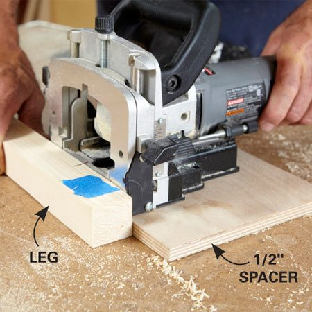 <b>Photo 6: Position the slot with a spacer</b></br> Place a scrap of 1/2-in. plywood or particleboard on the work surface. Butt the leg against it and rest the biscuit joiner on the spacer while you cut the slots. The 1/2-in. spacer will automatically position the slots.