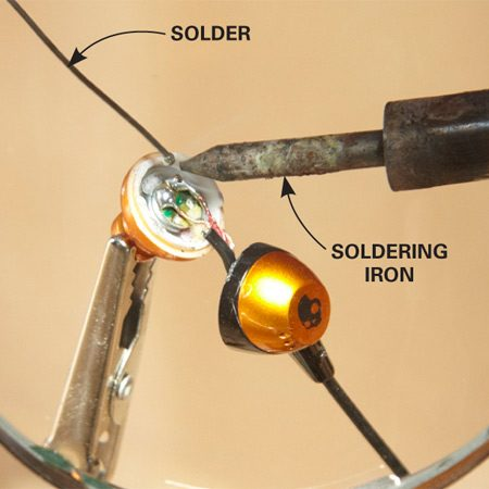 <b>Photo 2: Solder the connection</b></br> Place the wire on the circuit board and hold it in place with the tip of the soldering iron. Add solder. Then remove the hot iron and hold the wire in place until the solder cools.