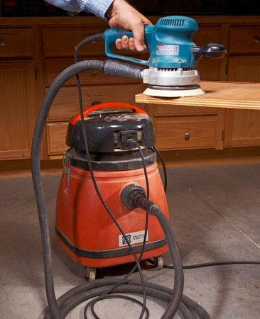 <b>Tool-actuated vacuum</b></br> 	<p>I spent years of my life hunched       over sanders and blowing my nose.       At least that's what it seems like.</p>       <p>This contraption changed all that.         It's a shop vacuum with a tool-actuated         switch, a long soft hose         and an adapter for a sander. My vac         is made by Fein; I like its low noise         level, but other vacs will do just fine.         The tool-actuated switch is handy         but not necessary. The rest of the         rig you have to cobble together.</p>       <p>You can get 1-1/4-in. hose         anywhere shop vacuums are sold,         though you may need two lengths,         and you can find rubber or plastic         adapters at woodworking stores or online (see the Fein step adapter,  available through our affiliation with <a href='http://www.amazon.com/gp/product/B00005M1SW/ref=as_li_qf_sp_asin_tl?ie=UTF8&tag=familhandy-20&linkCode=as2&camp=17'>Amazon.com</a>). But you may need hose         clamps, bits of rubber hose or even         a whittled block of wood to fit the         hose to your sanders. Persevere,         though. The joys of sanding without         a dust mask (and in a dust-free     shop) are priceless. </p>