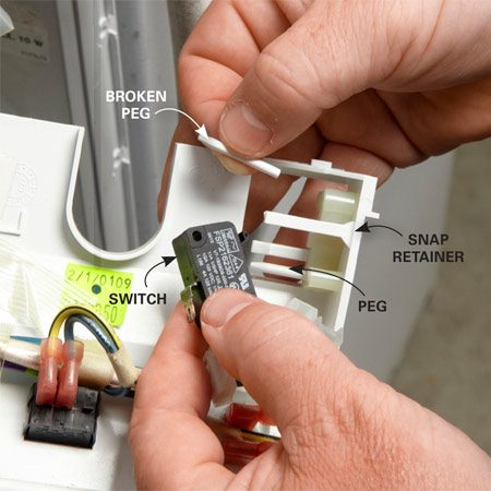 <b>Photo 2: Remove the microswitch</b></br> Pull the snap retainers away from the switch and slide it off the pegs.