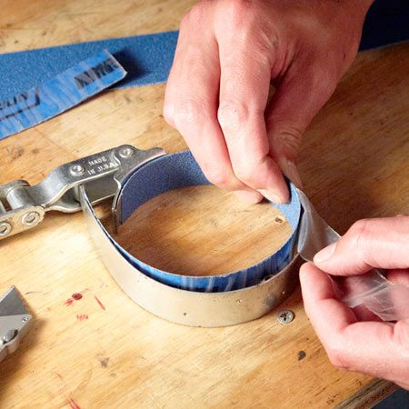 <b>Add grit to get a better grip</b></br> Slice a strip of adhesive-back sandpaper and slip it inside a band-style filter wrench. Then remove the adhesive liner and press it into place.