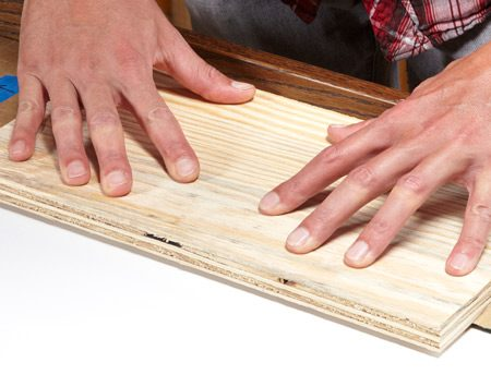<b>Photo 9: Press it into place</b></br> Make sure all sections are positioned right; adjust them if needed. Then press them hard against the mat with a scrap of plywood.