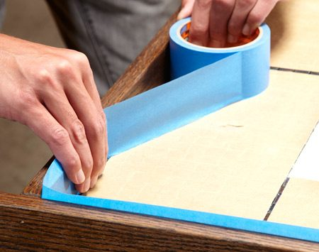 <b>Photo 10: Mask off the frame</b></br> Tape protects the frame from the grout.
