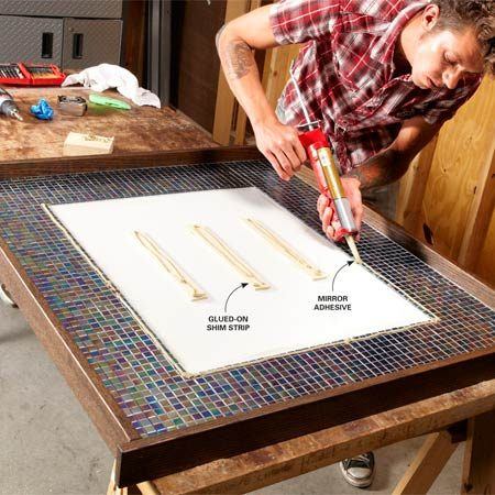 <b>Photo 13: Apply adhesive</b></br> <p>Cut wood strips the same   height as the tile and glue   them to the base. Then   apply mirror adhesive.   Also run mirror adhesive   around the inner edge of   the tile—just a thin bead   so it won't squeeze out   around the mirror. </p>