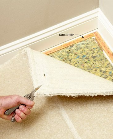 <b>Photo 1: Pull the carpet free</b></br> Grab the carpet right next to the baseboard and pull it straight up. Then loosen the rest of the carpet along the wall.