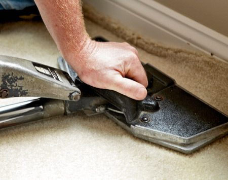 <b>Photo 3: Sink and stretch</b></br> <p>Set the  teeth into the carpet near the wall and push down on   the  stretcher handle. Then lock the stretched carpet into place by   jamming  it behind the tack strip with a putty or linoleum knife. </p>