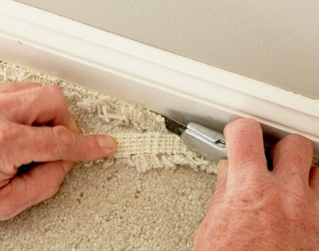 <b>Photo 4: Trim off excess carpet</b></br> Fold the excess carpet so the backing is facing up. Then cut it off with the carpet knife.