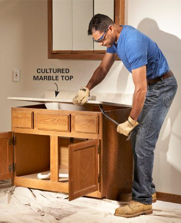 <b>Photo 1: Tear out the vanity</b></br> Disconnect the plumbing and pry off the old top. Then remove the vanity cabinet and old medicine cabinet or mirror.
