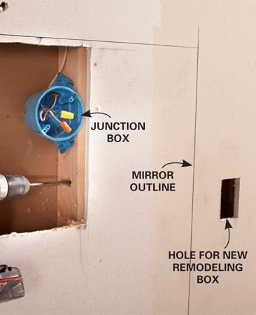 <b>Photo 3: Reroute electrical lines</b></br> Cut a large hole so it's easy to mount a new junction box and drill holes for the new wiring. Don't worry about patching the wall; the hole will be covered by the mirror.
