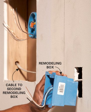 <b>Photo 4: Mount the new light boxes</b></br> Run a cable from the junction box to the new remodeling boxes. Slide the box into the hole and tighten the screws to clamp it onto the drywall.