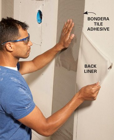<b>Photo 5: Apply the tile adhesive</b></br> Line up the edge of the Bondera tile adhesive with the tile line. Peel off the back liner as you press the adhesive to the wall.