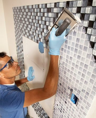 <b>Photo 8: Grout the tile</b></br> Press grout into the joints with a grout float. Sweep the float in diagonal strokes until the joints are completely filled. Then scrape off the excess grout with the edge of the float.