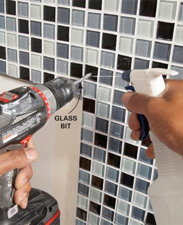 <b>Photo 12: Drill mirror clip holes</b></br> Keep the glass bit cool by spraying water on it as your drill. Run the drill at slow to medium speed. Let up on the pressure when you're almost through the tile.