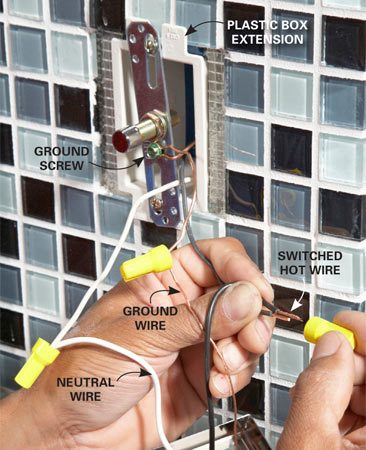 <b>Photo 14: Wire the light fixtures</b></br> Slip a box extension into the electrical box if the tile is more than 1/4 in. thick. Then mount the fixture strap to the box and connect the wires.