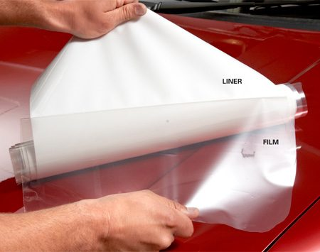 <b>Photo 1: Peel the adhesive liner and backer sheet and spray the film</b></br> Peel the liner partially off the sticky side of the film and immediately spray the adhesive with the detergent solution. Then place the wetted, sticky side down onto the prewetted hood. Remove the rest of the liner and backer sheet and spray the rest of the adhesive.