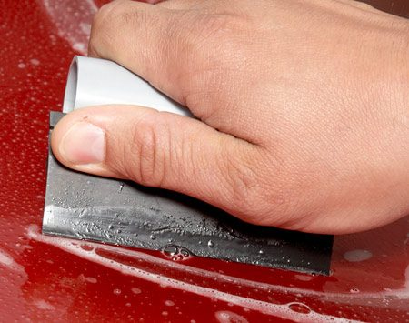 <b>Closeup</b></br> Squeegee small sections at a time. If it won't stick on curves, lift the film and spray it with the alcohol solution. Then squeegee again.