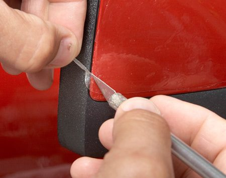 <b>Photo 4: Score and peel the excess</b></br> Lightly score the film around the edges and tear along the score line. Don't try to cut along the painted edge. You'll damage the paint.