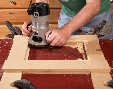 <b>Photo 2: Rout a groove first</b><br/><p>Clamp down   the long ends   of the frame,   remove the   plate and cut   a groove with   a pattern bit.   The bearing   guides the   bit perfectly   along the   inside of the   guide. </p>