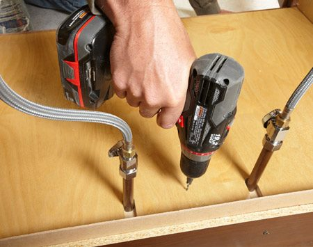 <b>Photo 2: Drop in the new floor and screw it into place</b></br> Predrill holes around the perimeter using a countersink bit. Then install brass-colored drywall screws.