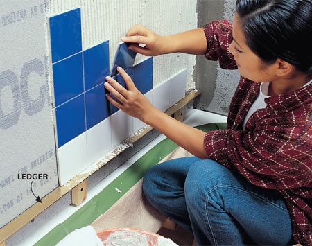 <b>Set tiles on a ledger</b></br> Fasten a straight ledger to the wall to support the tiles. Remove the ledger later and trim tiles to fill the gap below.