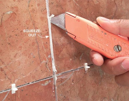 <b>Clean out the squeeze-out</b></br> Plow excess thin-set out of joints with a utility knife, a pencil or a tile spacer. Whatever you use, do it now, not later.