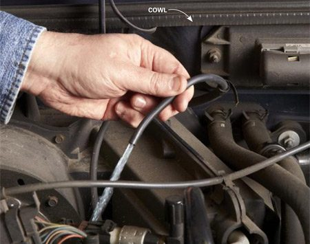 <b>Photo 1: Check pump operation</b></br> Follow the washer tubing from the reservoir to the tee. Disconnect the tubing and have a friend press the washer button. A strong stream of washer fluid indicates a good pump but a clogged nozzle.