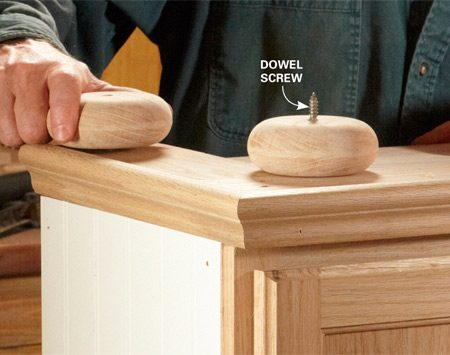 <b>Photo 3: Add the bun feet</b></br> Drive dowel screws halfway into the bun feet. Drill pilot holes in the bench base 2-1/4 in. from the edges and then screw in the bun feet.
