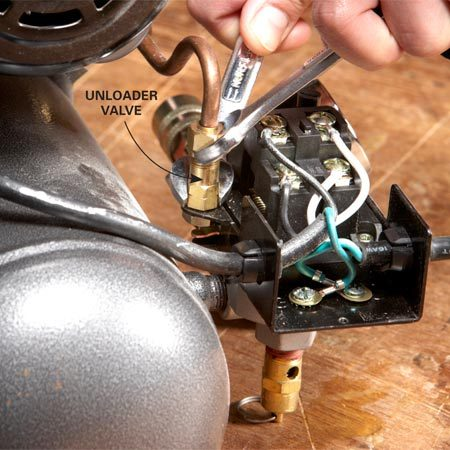 <b>Photo 1: Disconnect the unloader valve</b></br> Slap two open end wrenches on the compression fitting and loosen the nut on the air line. Pull it out of the fitting.