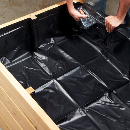 <b>Photo 6: Staple the rubber membrane in place</b></br> Fold the pond liner at the corners and staple it around the perimeter. Trim the excess.
