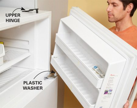 <b>Photo 1: Lift off the door</b></br> Tilt the upper door away from the fridge and lift it up and off the middle hinge pin. Immediately check for a plastic washer or guide that fits into the bottom of the upper door. Locate those parts and put them in a safe place.