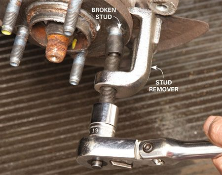 <b>Photo 1: Pull the broken wheel stud</b></br> Place the remover around the head of the broken wheel stud, behind the hub. Center the driving screw over the stud and tighten it with a ratchet until the stud pops out the back.