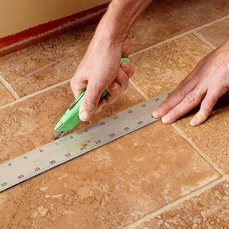 <b>Photo 1: Score the vinyl flooring</b></br> Measure out 10 in. from the wall and score the vinyl flooring with a utility knife. Then repeat scoring every 10 in. all the way across the room.