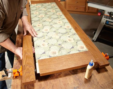 "<b>Photo 6: Put it all together</b></br> <p>Glue both  rails to one stile, then insert the panel. Work the   panel  into the dadoes carefully to prevent wallpaper ""roll back.""   Finally,  add the other stile, make sure the whole assembly is   square  and clamp it together. </p>"