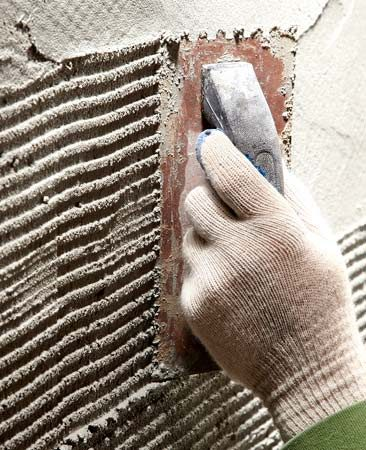 <b>Scratching the mortar</b></br> An inexpensive notched tile trowel works well to prepare the mortar for solid bonding.