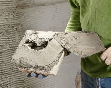 <b>Apply mortar to the veneer stone</b></br> Apply mortar to the backside perimeter of the veneer stone and press it in place.