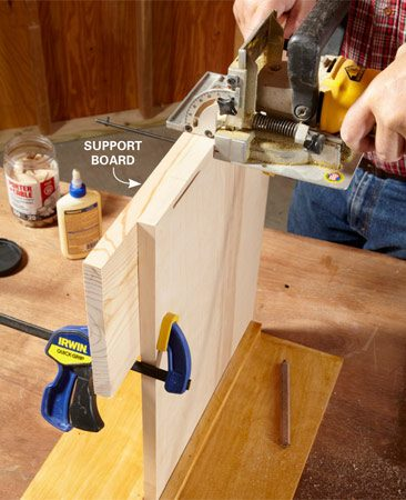 <b>Photo 3: Cut the biscuit slots</b></br> Clamp a support board flush with the edge to keep the biscuit joiner from rocking as you cut.