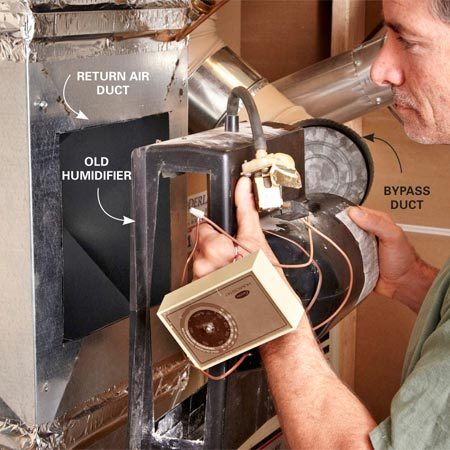 <b>Photo 1: Disconnect and remove the furnace humidifier that doesn't work</b><br/><p>Remove  the screws from the bottom of the old   humidifier.  Then unscrew the fasteners at the top. Tilt   the top  out and lift it off the duct or plenum. </p>
