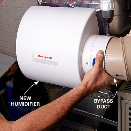 <b>Photo 3: Install the bypass</b></br> <p>Install  the summer/winter   damper  (provided with the new furnace humidifier)   and  insert the bypass duct. Secure it   with  sheet metal screws. </p>