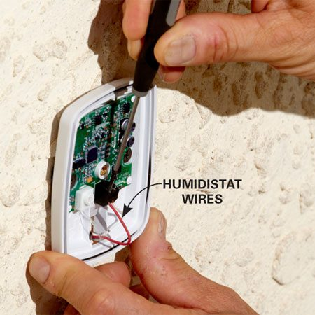 <b>Photo 4: Install the outdoor temperature sensor</b></br> Connect the thermostat cable to the outdoor sensor. Then push the extra wire back into the hold and caulk the hole. Mount the sensor to your house.