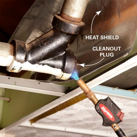 <b>Photo 1: Heat the cleanout plug and fitting</b></br> <p>Clean  away any cobwebs, and   shield  surrounding wood with a metal   baking  pan. Grab a soldering torch and   apply  just enough heat to warm the cleanout plug and   fitting.  Don't get it cherry red. </p>